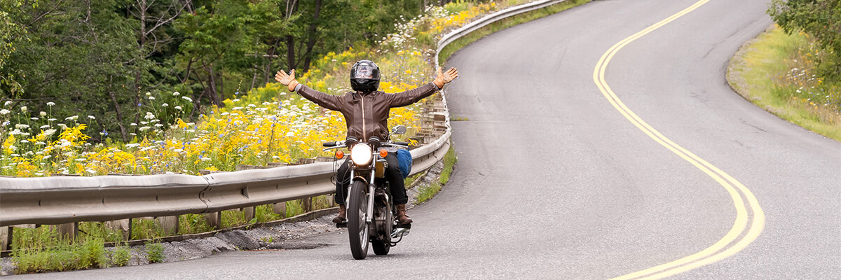 A man riding a motorcycle with no hands down a beautiful country road