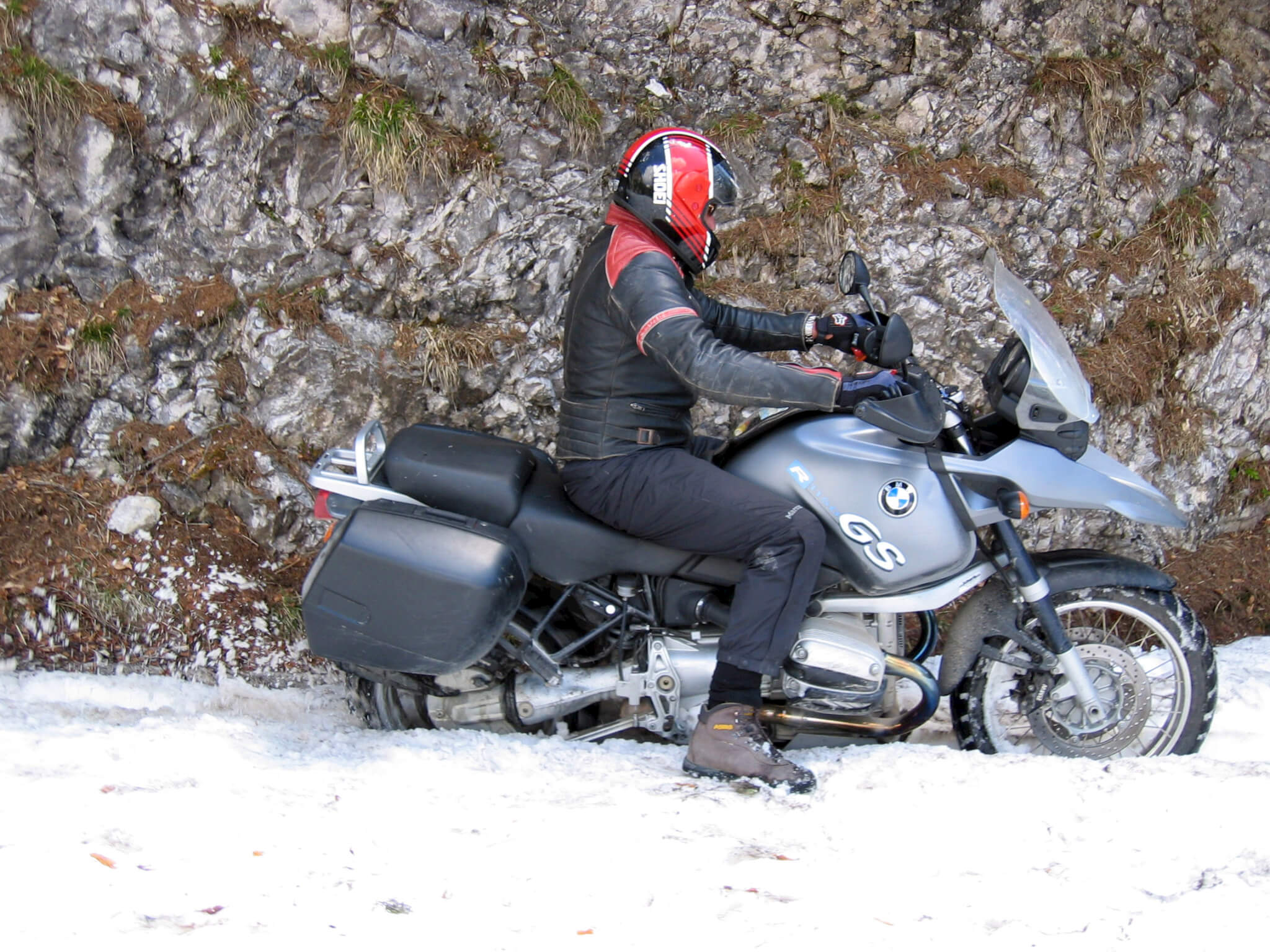 A man riding his motorcycle in the early spring, snow is on the ground