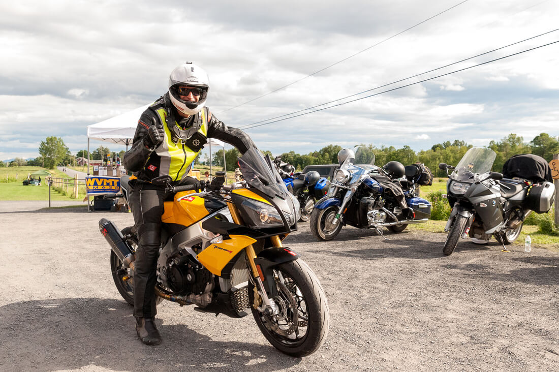 A man gives the camera a thumbs up as he sits on a yellow motorcycle