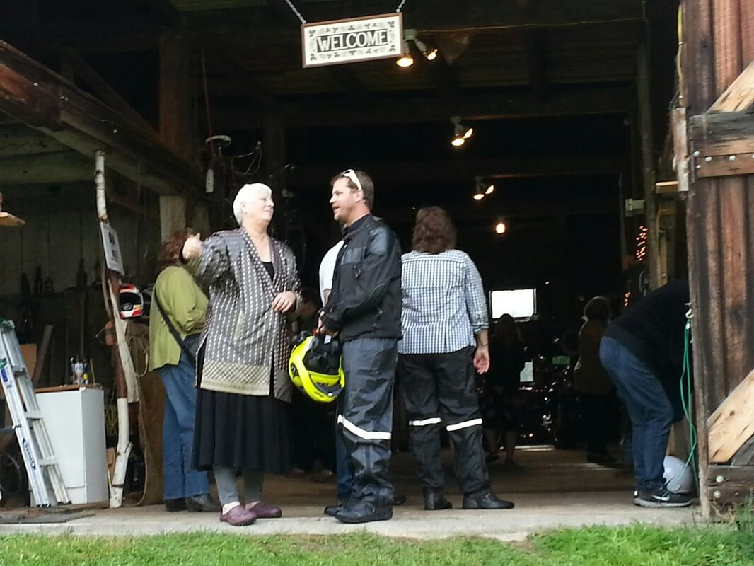 A woman speaks to a motorcyclist at the entry to a wooden barn