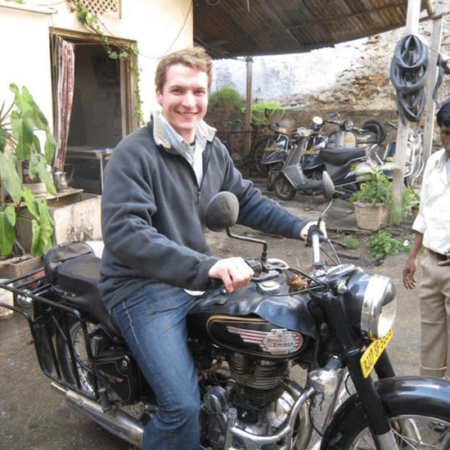 Portrait of Andrew Stickney on an antique motorcycle in India