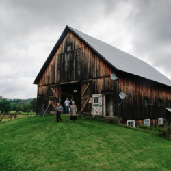 Exterior view of rustic barn on a lush green landscape, overcast sky