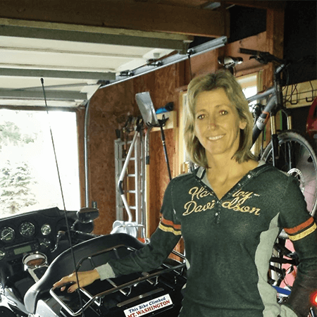 Portrait of Debby Pearson, posing in front of he motorcycle and standing in her garage