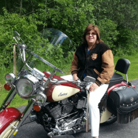 Portrait of Heidi Clute sitting on her Harley Davidson motorcycle