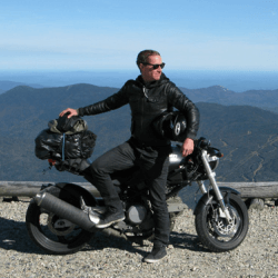Portrait of Jeremy Kent on this motorcycle in front of a mountain landscape