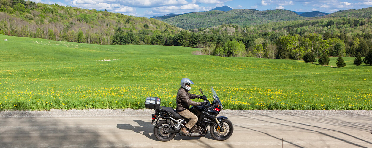 A man riding his motorcyle on a dirt road in Vermont