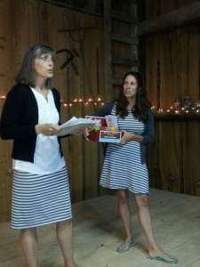 Two women in striped dresses pitch and idea to investors