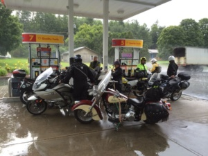 Motorcyclists take refuge from a thunderstorm at a Shell gas station