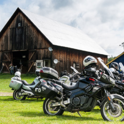 Motorcycles parked outside a beautiful wooden barn on a sunny day