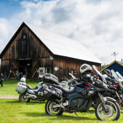 Motorcycles lined up outside a wooden barn on a sunny day