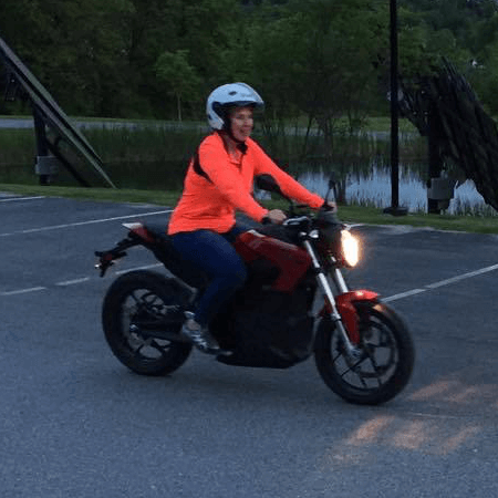 Portrait of Debra Sachs riding her motorcycle at dusk