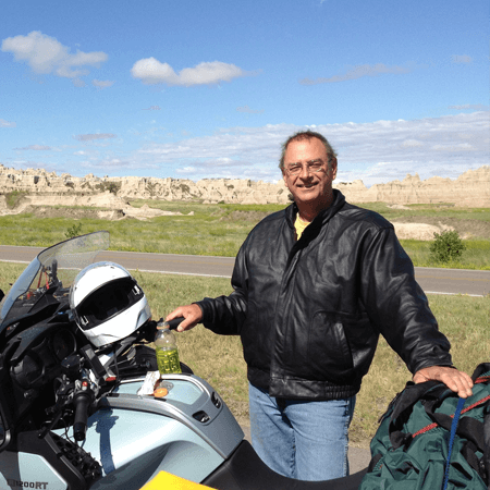Portrait of David Blittersdorf standing next to his motorcycle in a desert landscape