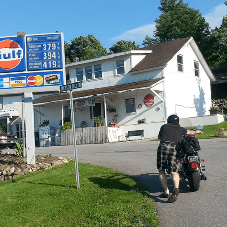 Portrait of Doug Webster pushing is motorcycle up the road to a gas station
